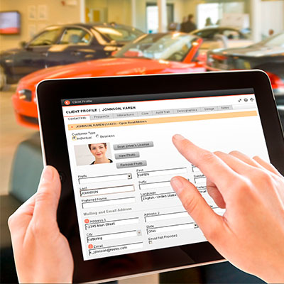 Dealership employee using contact management on a tablet device.