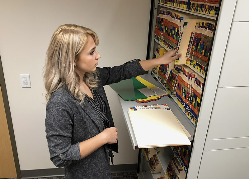 Young woman filing folders using ColorFile filing system.